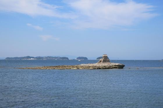 沖の岩場に祠が建っている